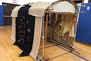 Mini Longhouse draped with tapestries and animal pelts.