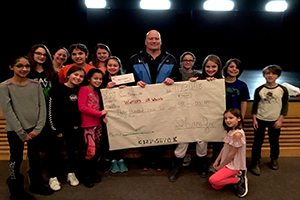 Students in the SHARE Jr Club present Ned with an oversized check for $306.00.