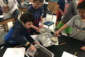 Students filtering water from a simulated mudslide.