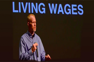 "Jim Keady in front of a projection screen that says ""Living Wages""."