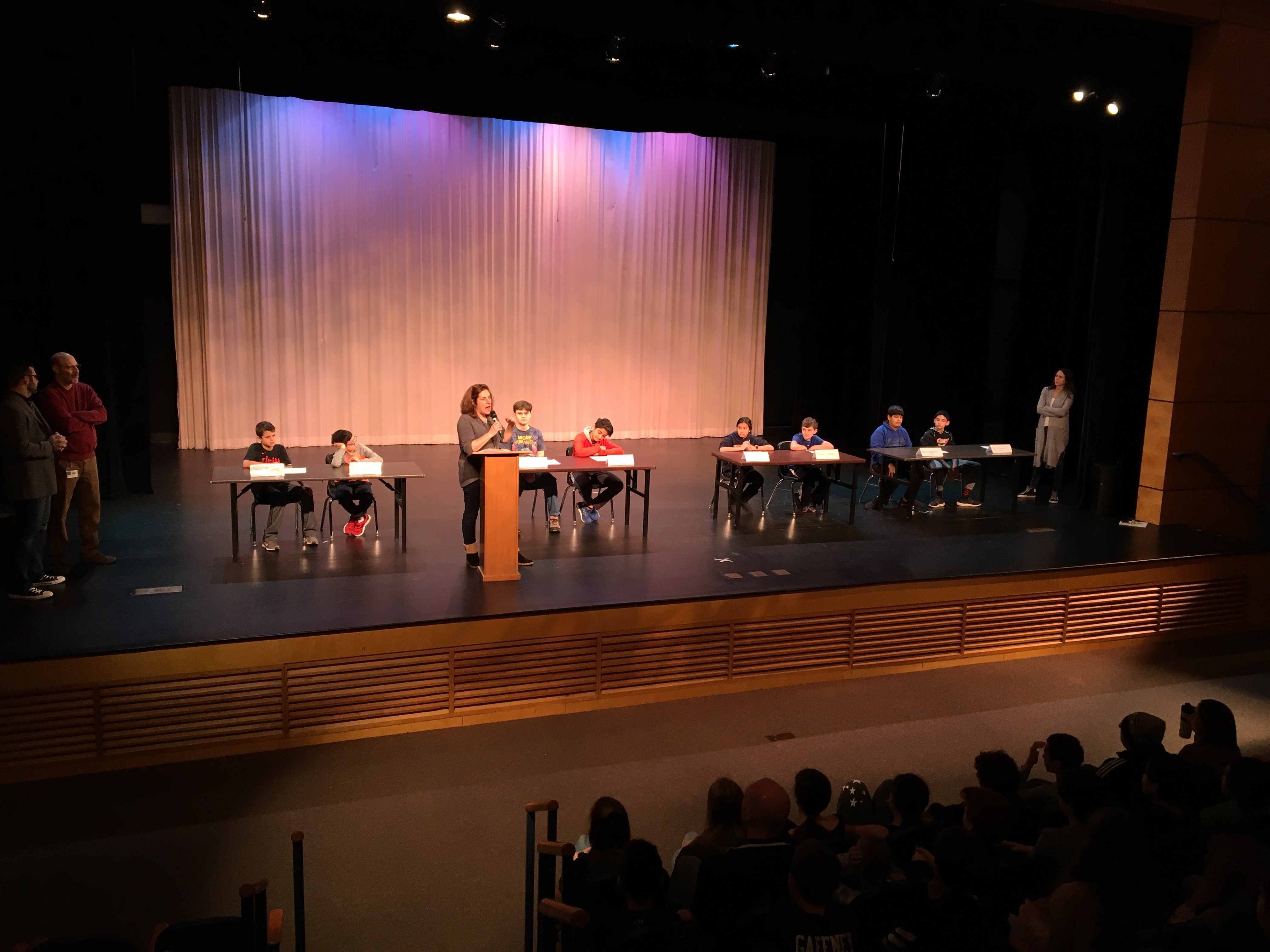 National Geography Bee. Contestants seated at tables on a stage.
