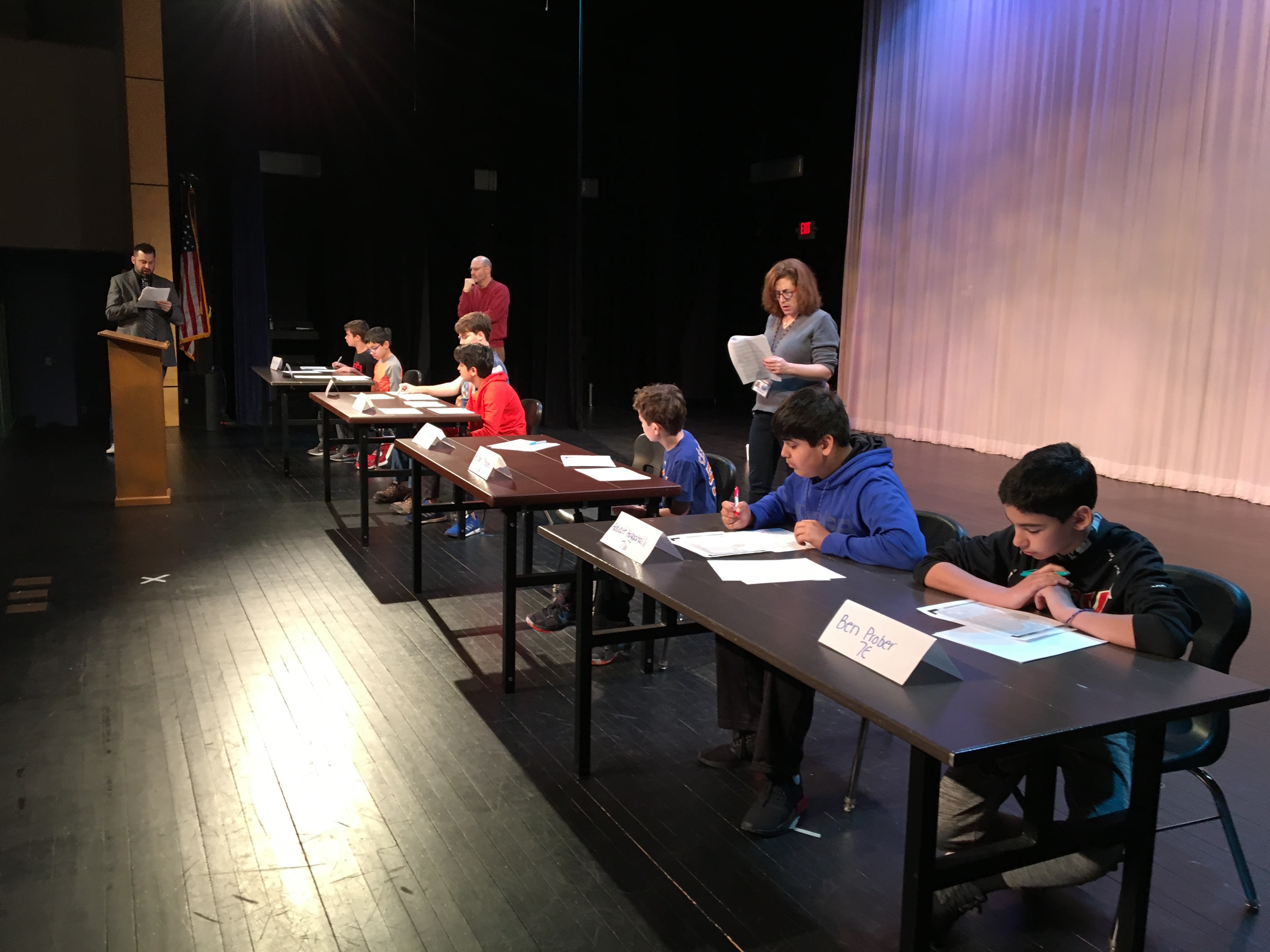 National Geography Bee. Contestants seated at tables on a stage andwering questions.