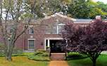 Exterior of the Ed Center, a brick building with trees and a staricase out in front